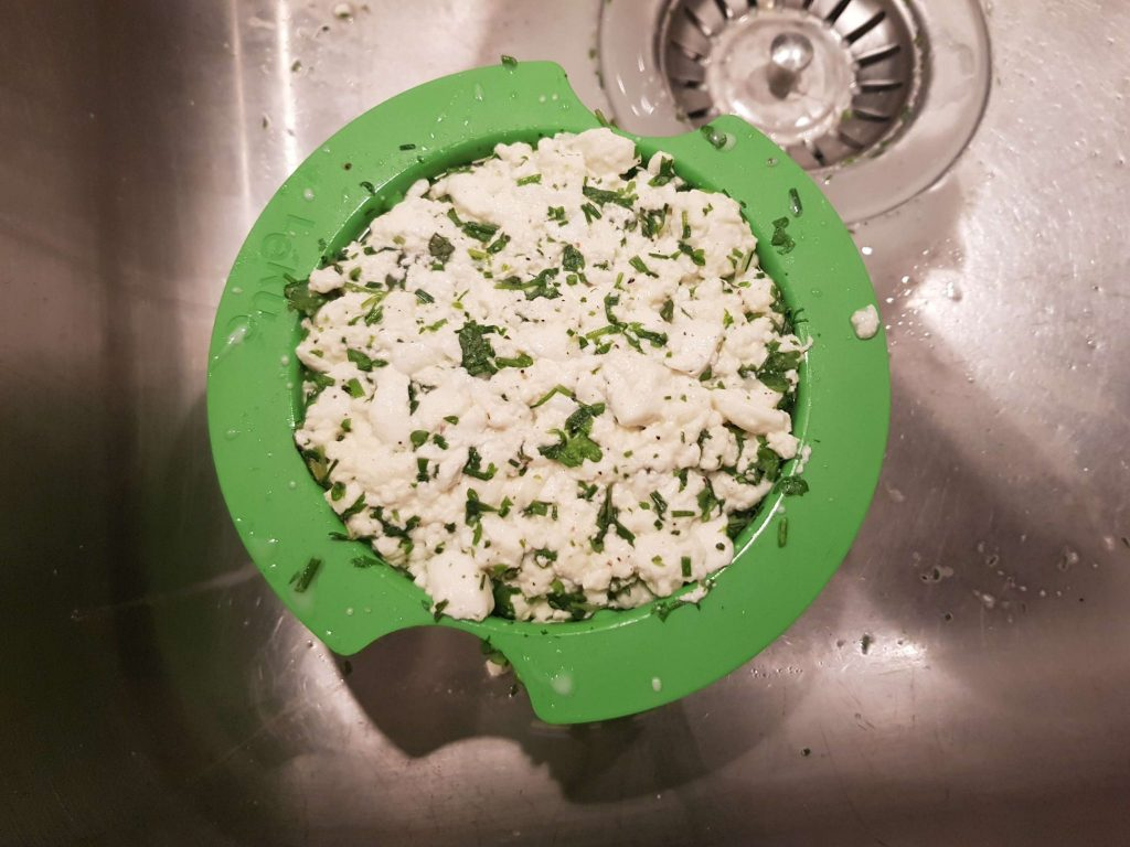 Når ostemassen er hældt gennem sien, er det kun klumperne, der er tilbage.
